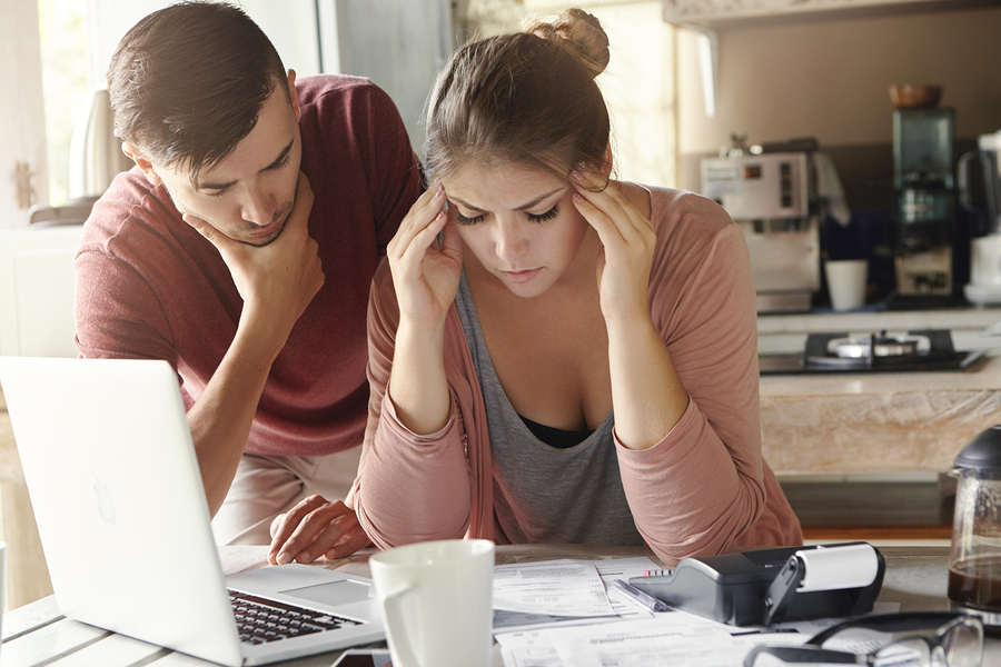 Young family with many debts facing financial stress. Unemployed male looking pensive standing next to his depressed wife with headache who is calculating expenses trying to make both ends meet